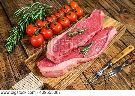 Raw Top Sirloin Cap Or Picanha Steak On A Chopping Board. Wooden Background. Top View