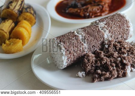 Steamed Finger Millet And Coconut Cake Served With Sardines Curry And Steamed Plantain.