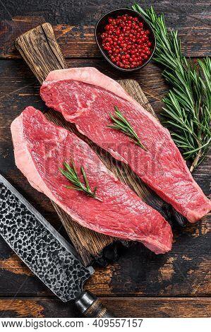 Raw Beef Meat Cap Sirloin Steak On A Cutting Board. Dark Wooden Background. Top View