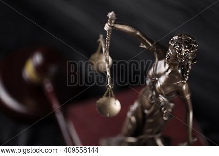 The Statue Of Justice - Lady Justice Or Justitia The Roman Goddess Of Justice. Statue On Brown Book