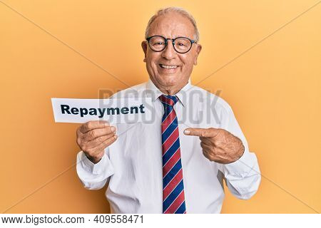 Senior caucasian man holding repayment word paper smiling happy pointing with hand and finger