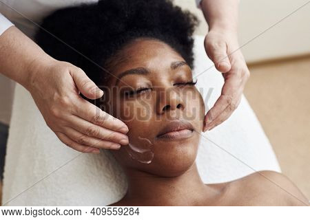A Young Black Woman Lies In The Beauticians Office And Relaxes From Gentle Touches And Toning Massag