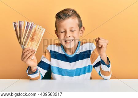 Adorable caucasian kid holding 500 norwegian krone banknotes sitting on the table screaming proud, celebrating victory and success very excited with raised arm