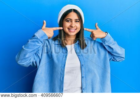 Young latin woman wearing cute wool cap smiling cheerful showing and pointing with fingers teeth and mouth. dental health concept.