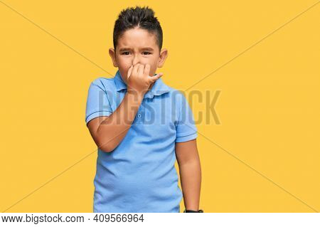 Little boy hispanic kid wearing casual clothes smelling something stinky and disgusting, intolerable smell, holding breath with fingers on nose. bad smell