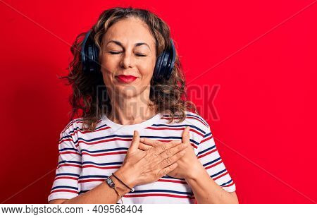 Middle age brunette woman listening to music using headphones over red background smiling with hands on chest, eyes closed with grateful gesture on face. Health concept.