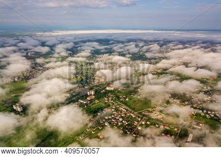 Aerial View Of White Clouds Above A Town Or Village With Rows Of Buildings And Curvy Streets Between