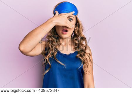 Young blonde girl wearing sleep mask and pyjama peeking in shock covering face and eyes with hand, looking through fingers afraid