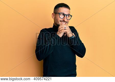 Handsome man with tattoos wearing turtleneck sweater and glasses laughing nervous and excited with hands on chin looking to the side