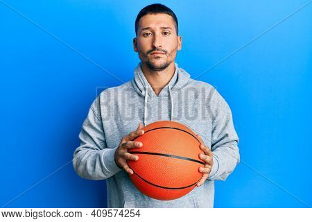 Handsome man with tattoos holding basketball ball relaxed with serious expression on face. simple and natural looking at the camera.