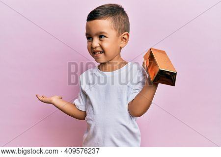 Adorable latin toddler holding gold ingot celebrating achievement with happy smile and winner expression with raised hand