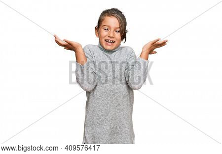 Little beautiful girl wearing casual turtleneck sweater celebrating victory with happy smile and winner expression with raised hands