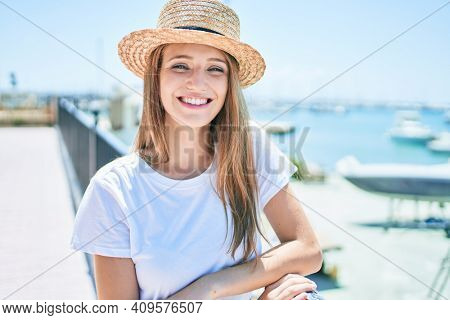 Young blonde woman on vacation smiling happy leaning on balustrade at street of city