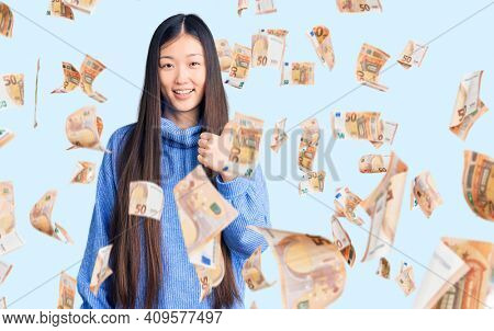 Young beautiful chinese woman wearing casual turtleneck sweater doing happy thumbs up gesture with hand. approving expression looking at the camera showing success.