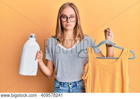 Beautiful blonde woman holding shirt on hanger and detergent bottle relaxed with serious expression on face. simple and natural looking at the camera.