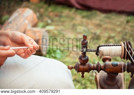 Hands Of A Woman Demonstrating Traditional Wool Spinning On An Old Spinning Wheel.