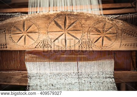An Old Hand-weaving Vintage Wooden Loom Being Used To Make Fabric. Traditional European Solar Symbol