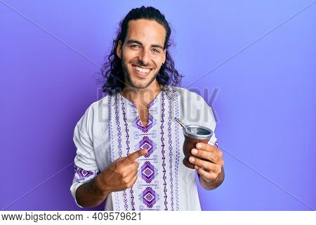Young handsome man with long hair drinking mate infusion smiling happy pointing with hand and finger