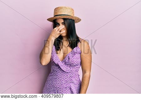 Young brunette woman wearing summer dress and hat smelling something stinky and disgusting, intolerable smell, holding breath with fingers on nose. bad smell