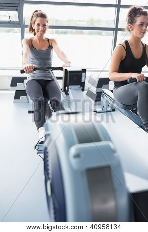 Two people training on row machines in gym