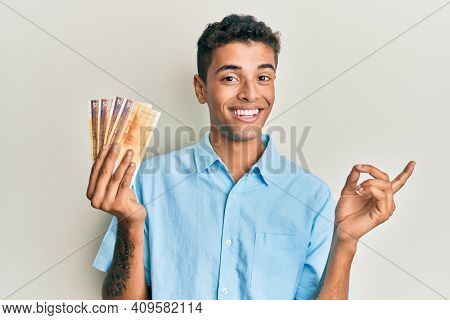 Young handsome african american man holding 500 norwegian krone banknotes smiling happy pointing with hand and finger to the side
