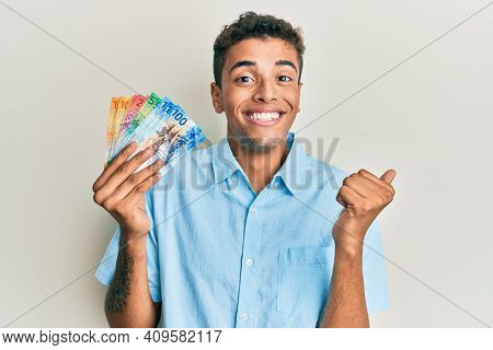Young handsome african american man holding swiss franc banknotes screaming proud, celebrating victory and success very excited with raised arm