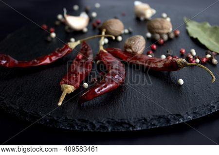 Hot Bright Chili Peppers, Salt And On A Slate Board On A Black Background Close Up Front View Narrow
