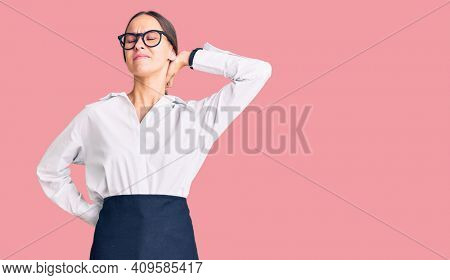 Beautiful brunette young woman wearing professional waitress apron suffering of neck ache injury, touching neck with hand, muscular pain