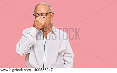 Senior caucasian man wearing business shirt and glasses tired rubbing nose and eyes feeling fatigue and headache. stress and frustration concept.