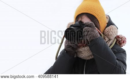 Portrait Of A Little Girl And Holding Camera On A White Background. Little Girl Photographer In Wint