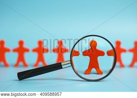 The View Through The Magnifier On The One Wooden Red Person Between Other People. Looking For Employ