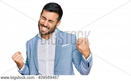 Young hispanic man wearing business jacket very happy and excited doing winner gesture with arms raised, smiling and screaming for success. celebration concept.