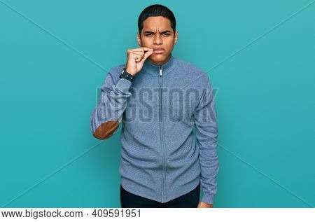 Young handsome hispanic man wearing casual sweatshirt mouth and lips shut as zip with fingers. secret and silent, taboo talking