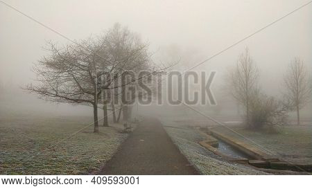 Road In The Park During Misty Morning. The Atmosphere Looks Mysterious But Beautiful In The Same Tim