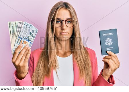 Young blonde woman wearing business style holding dollars and usa passport relaxed with serious expression on face. simple and natural looking at the camera.