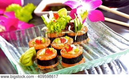 A Sushi Set. Special Salmon Rolls With Avocado And Caviar On A Glass Plate.