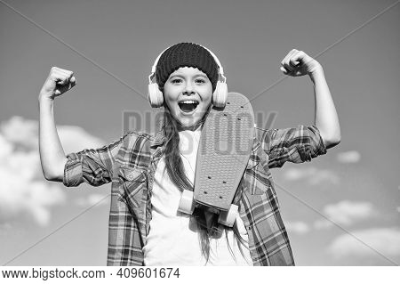 Girl Power. Happy Skater Flex Arms On Blue Sky. Little Child With Penny Board Outdoors. Power Slide