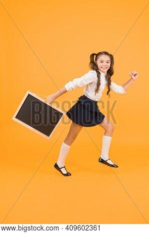 Little And Energetic. Little Child Carrying Blackboard On Yellow Background. Little Schoolgirl With