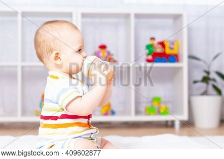 Cute Caucasian Baby Boy Drinking From Bottle Fruit Tea With Camomile. Sitting On White Carpet In Str