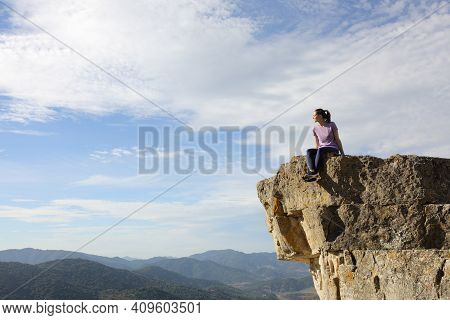 Runner Resting Sitting Contemplating Views From The Top Of A Cliff In The Mountain