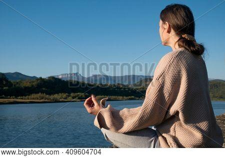 woman is practicing yoga in lotus pose at mountain lake