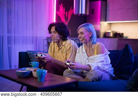 Young Cheerful Caucasian Husband And Wife Play Videogames Against Each Other At Home Enjoying Leisur