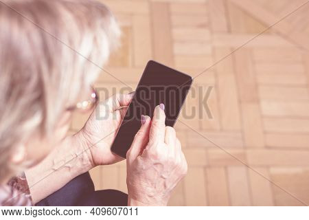 Elderly Womans Hand Holding Mobile Cell Phone. Over Shoulder. Old Woman Looking At Cell Phone. Close
