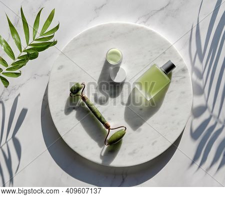 Jade Face Roller And Herbal Infusion For Facial Massage Therapy. Flat Lay On Round Marble Podium On