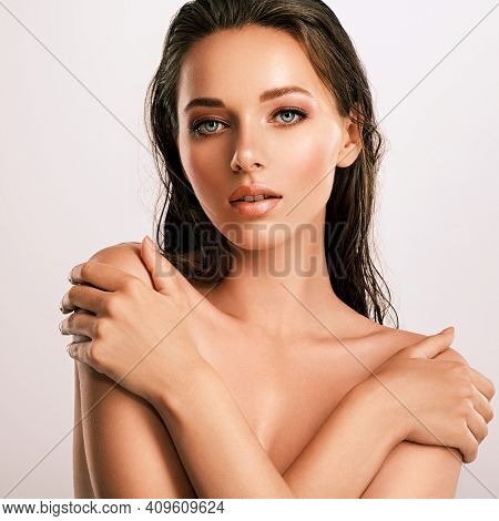 Closeup  portrait of an attractive caucasian girl with wet hair. Model with bright brown eye makeup. Skin care concept.  Young beautiful woman with healthy skin of face.