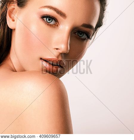 Young beautiful woman with healthy skin of face. Closeup  portrait of an attractive caucasian girl with wet hair. Model with bright brown eye makeup. Skin care concept.