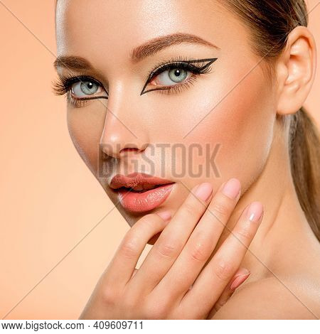 Beautiful girl with makeup in the form of arrows. Face of a young girl close-up with fashionable makeup over beige background. Stylish makeup.