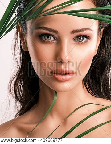 Young beautiful woman with green leaves near face and body. Skin care beauty treatments concept.  Closeup girl's face with green leave. White model with clean, health skin of face - posing at studio