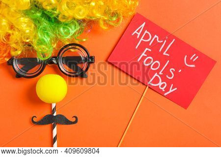 Funny Face Made Of Clown's Accessories And Sign With Phrase April Fools' Day On Red Background, Flat