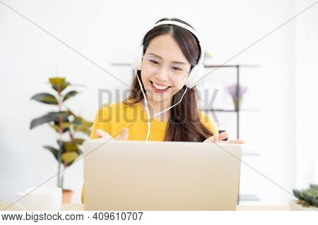 Asian Young Woman Student Wear Wireless Headset Video Conference Calling On Laptop Computer Talk By